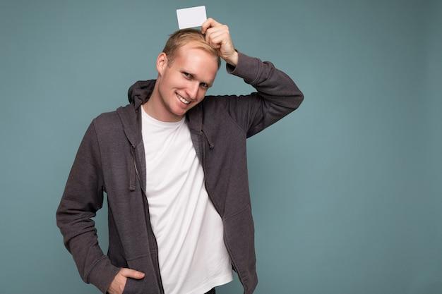 Foto van een knappe gelukkig lachende blonde man met een grijze trui en een wit t-shirt geïsoleerd over een blauwe achtergrondmuur met een creditcard die naar de camera kijkt. kopieer ruimte