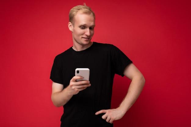 Foto van een knappe glimlachende positieve jonge blonde man geïsoleerd over een rode achtergrondmuur die een zwart t-shirt draagt en een mobiele telefoon gebruikt die sms schrijft en naar de camera kijkt.