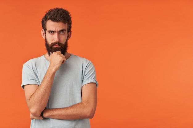 Foto van een knappe jonge bebaarde man met bruine ogen in een wit t-shirt in casual stijl, recht tegen de rode muur staande arm aanraken baard emotie scepticus twijfelaar cynicus