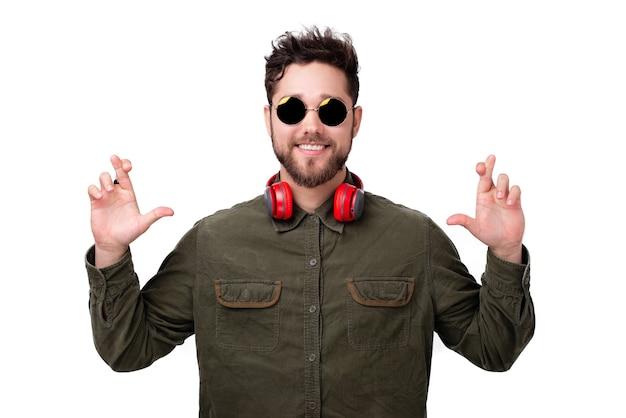 Foto van een knappe jongeman die een zonnebril draagt en zijn vinger kruist voor geluk