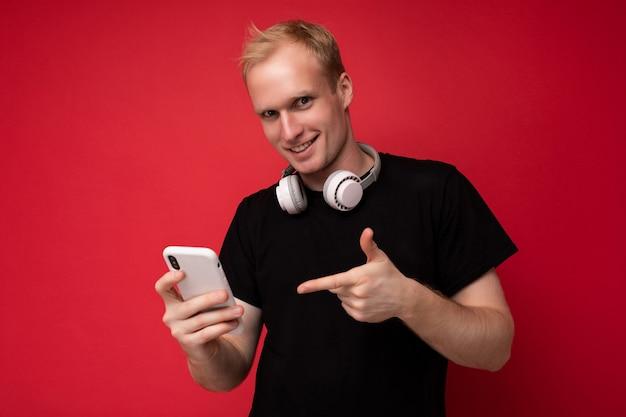 Foto van een knappe knappe blonde jongeman met een zwart t-shirt en een witte koptelefoon die staat?