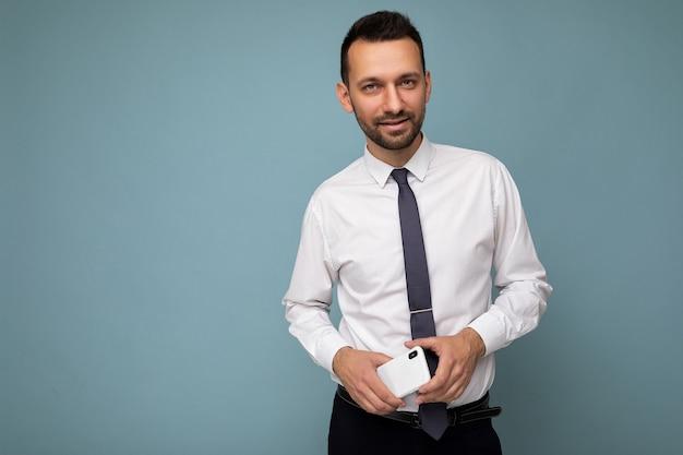 Foto van een knappe, knappe brunet ongeschoren man met baard die een casual wit overhemd en stropdas draagt