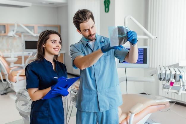 Foto van een knappe tandarts die bij haar collega staat en röntgenfoto's vasthoudt.