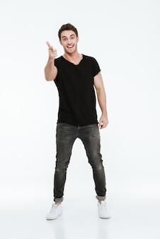 Foto van een knappe vrolijke jongeman gekleed in een zwart t-shirt dat op een witte achtergrond staat en naar de camera wijst.