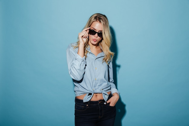 Foto van een koele blonde vrouw in shirt en zonnebril