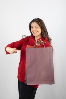 Foto van een lachende dame wijzend op kleurrijke boodschappentassen.