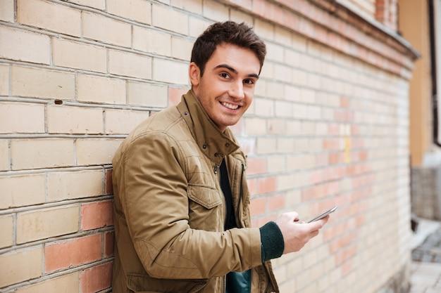 Foto van een lachende jonge man die op straat loopt en buiten aan het chatten is met zijn telefoon. kijk naar de camera.