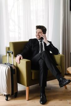 Foto van een lachende jonge zakenman in een zwart pak die op zijn mobiel praat terwijl hij op een fauteuil in een hotelappartement zit