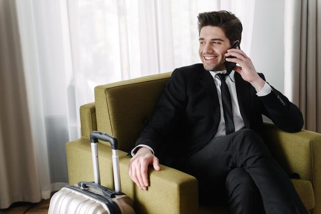Foto van een lachende knappe zakenman in een zwart pak die op zijn mobiel praat terwijl hij op een fauteuil in een hotelappartement zit