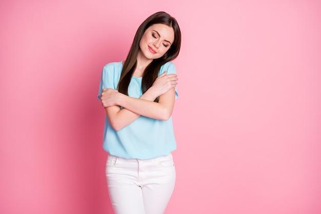 Foto van een leuk, schattig, lief meisje omhels zichzelf en geniet van zelfliefde geïsoleerd op een pastelkleurige achtergrond