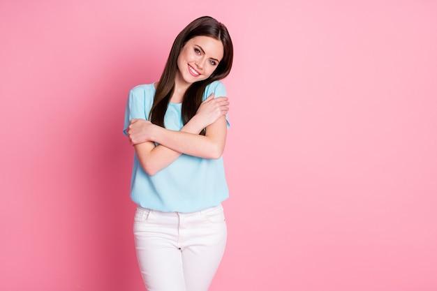 Foto van een leuk schattig mooi meisje dat zichzelf omhelst, zelfliefde draagt en een blauwe witte broek draagt, geïsoleerd op een pastelkleurige achtergrond