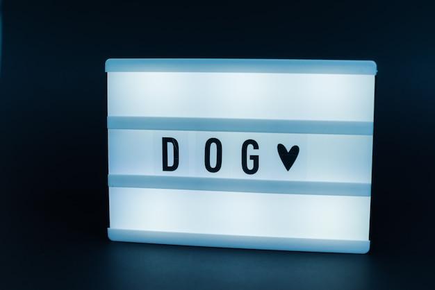 Foto van een lichtbak met tekst, hond, over geïsoleerde donkere muur