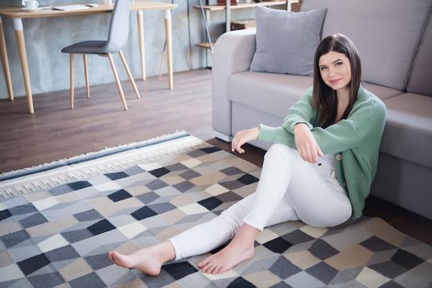Foto van een lief, vredig meisje dat in huis op de vloer zit