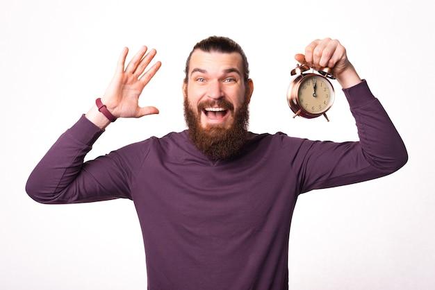 Foto van een man die een klok vasthoudt en opgewonden is, kijkt naar de camera