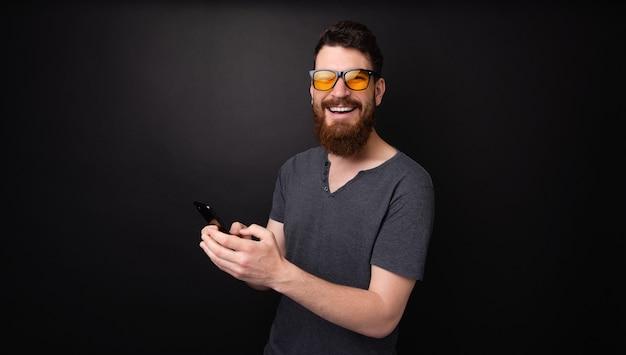 Foto van een man met een baard die een stijlvolle zonnebril draagt en een mobiel vasthoudt terwijl hij naar de camera kijkt