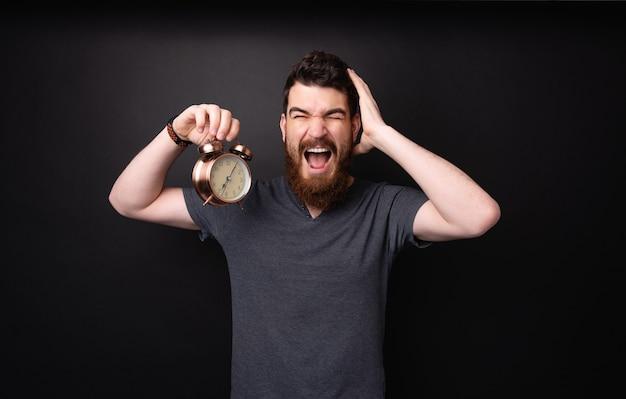 Foto van een man met een baard die een vintage klok vasthoudt, vertraging oploopt en zich zorgen maakt over discipline