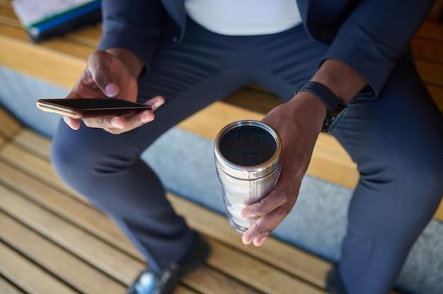 Foto van een man met een telefoon en een fles water in handen