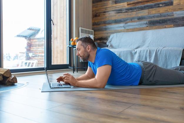 Foto van een man van middelbare leeftijd tijdens een online videogesprek. hij ligt op de grond terwijl hij voor een laptopmonitor staat.