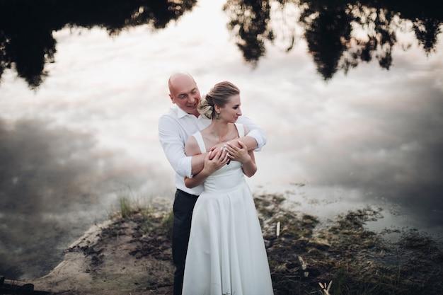 Foto van een man zonder haar in wit overhemd en zwarte broek met een vrouw met blond haar in lange witte jurk bij het meer