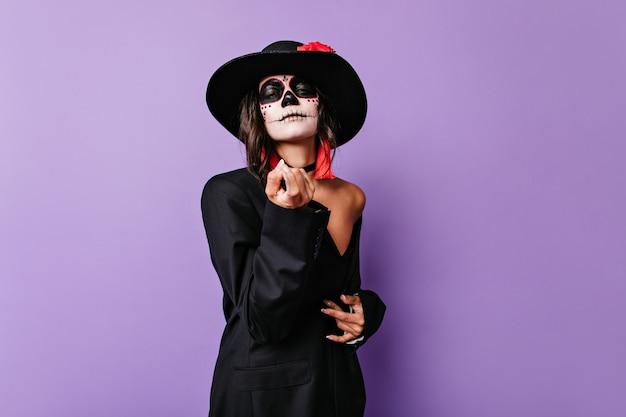 Foto van een meisje met een zwarte hoed met brede rand, die zichzelf uitnodigt. mexicaans model met schedelmake-up poseren in oversized jas.