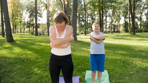 Foto van een moeder van middelbare leeftijd met haar tienerjongen die yoga- en ademhalingsoefeningen doet in het park. familie zorgt voor hun mentale en fysieke gezondheid tijdens het sporten