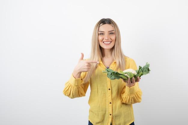 Foto van een mooi glimlachend vrouwenmodel met bloemkool die een duim toont.