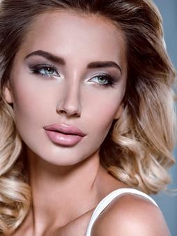 Foto van een mooi jong blond meisje met krullend haar. close-up aantrekkelijk sensueel gezicht van blanke vrouw met lang haar. smokey-oogmake-up.