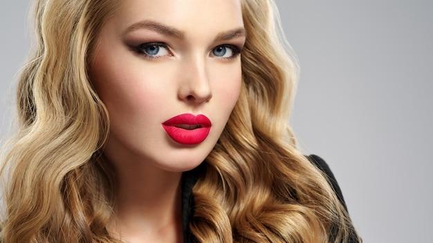 Foto van een mooi jong blond meisje met sexy rode lippen. close-up aantrekkelijk sensueel gezicht van blanke vrouw met lang haar. rokerige oogmake-up
