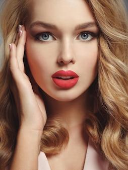 Foto van een mooi jong blond meisje met sexy rode lippen. close-up aantrekkelijk sensueel gezicht van blanke vrouw met lang krullend haar.