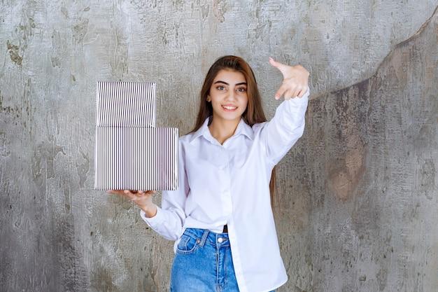 Foto van een mooi meisjesmodel dat dozen met cadeautjes vasthoudt en naar beneden wijst