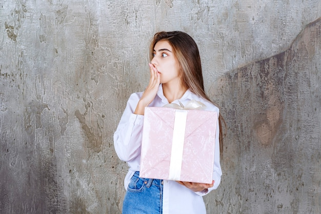 Foto van een mooi meisjesmodel met een groot cadeau dat de mond bedekt met de hand