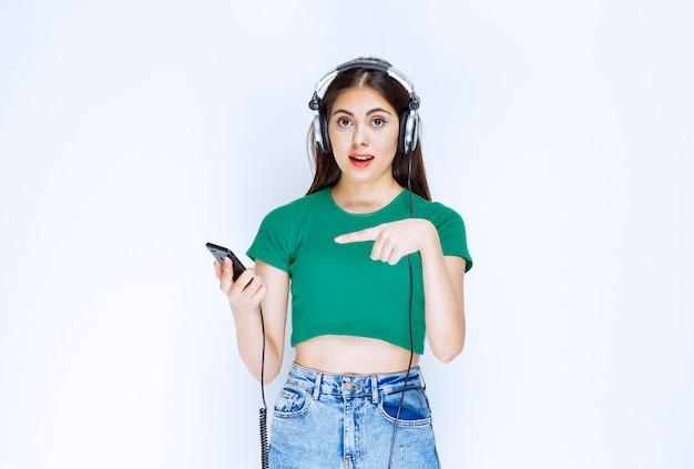 Foto van een mooi meisjesmodel met hoofdtelefoons die op mobiele telefoon wijzen.