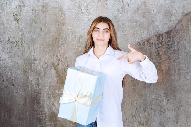Foto van een mooi meisjesmodel met lang haar dat naar een groot cadeau wijst