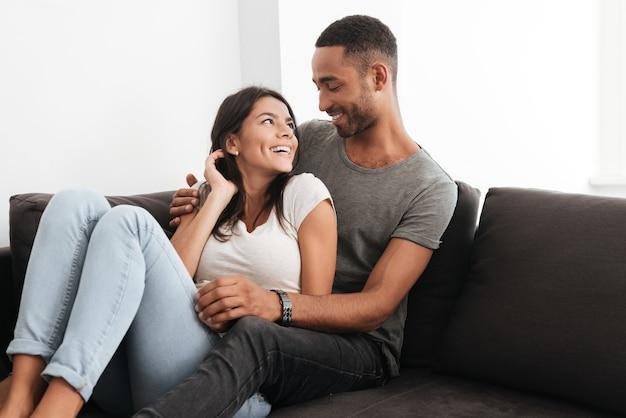 Foto van een mooi paar dat thuis op een bank lacht. elkaar aankijken.