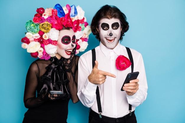 Foto van een mooi spookachtig stel man dame houdt directe vinger telefoon vind ondode vriend sociaal netwerk draag zwarte jurk dood kostuum rozen hoofdband bretels geïsoleerde blauwe kleur achtergrond