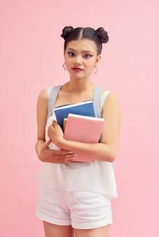 Foto van een mooi studentenmeisje van de jaren '20 met een kapsel met dubbele broodjes en een rugzak met veel studieboeken geïsoleerd op een roze achtergrond