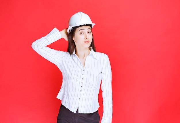 Foto van een mooie bedrijfsvrouw die een veiligheidshoed draagt die zich tegen rode muur bevindt.