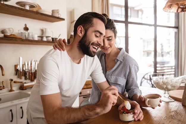 Foto van een mooie brunette paar man en vrouw die koffie drinken en desserts eten tijdens het ontbijt in de keuken thuis