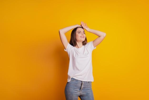 Foto van een mooie dromerige dame die eruitziet als een lege ruimte, draag een wit t-shirt op een gele achtergrond