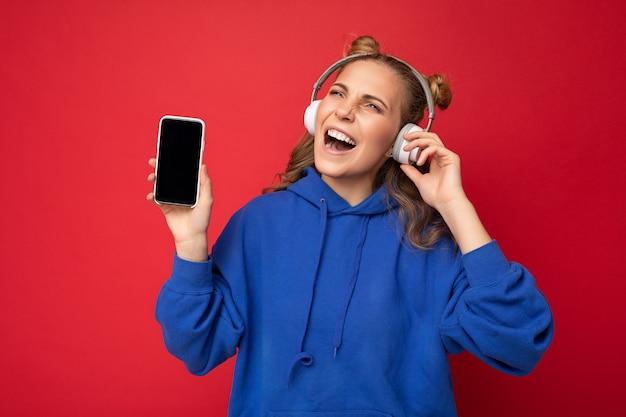 Foto van een mooie gelukkig lachende jonge vrouw die een stijlvolle blauwe hoodie draagt, geïsoleerd over rood