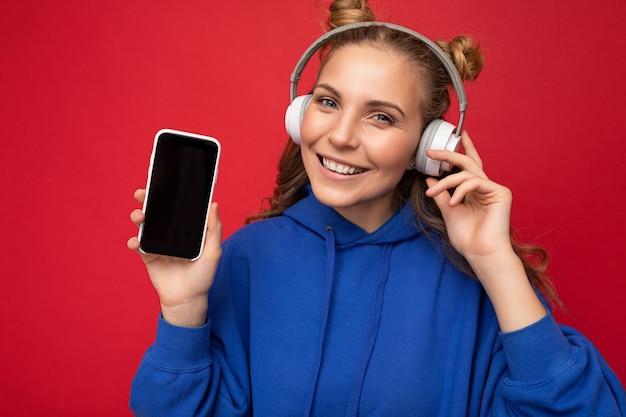 Foto van een mooie glimlachende jonge vrouw die een stijlvolle blauwe hoodie draagt, geïsoleerd op een rode achtergrond