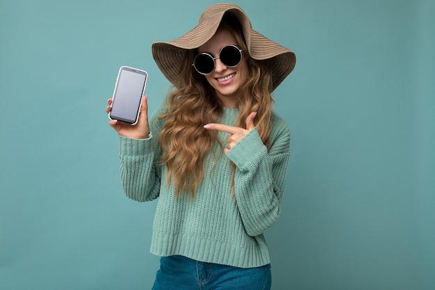 Foto van een mooie glimlachende jonge vrouw die er goed uitziet met een casual stijlvolle outfit die geïsoleerd staat