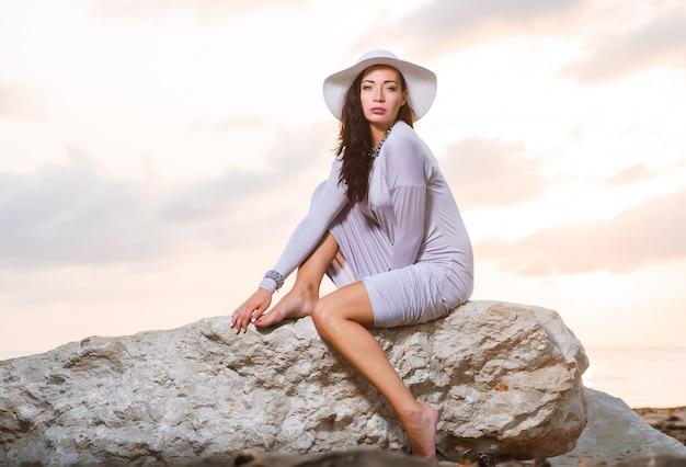 Foto van een mooie jonge elegante vrouw in een hoed aan zee