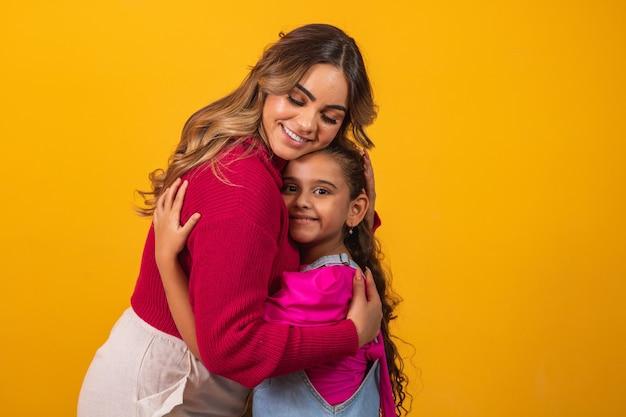 Foto van een mooie jonge mama die haar armen vasthoudt en haar dochtertje knuffelt goed humeur schattig oprecht hartgevoel in de rug jeans t-shirts geïsoleerd met gele kleur achtergrond