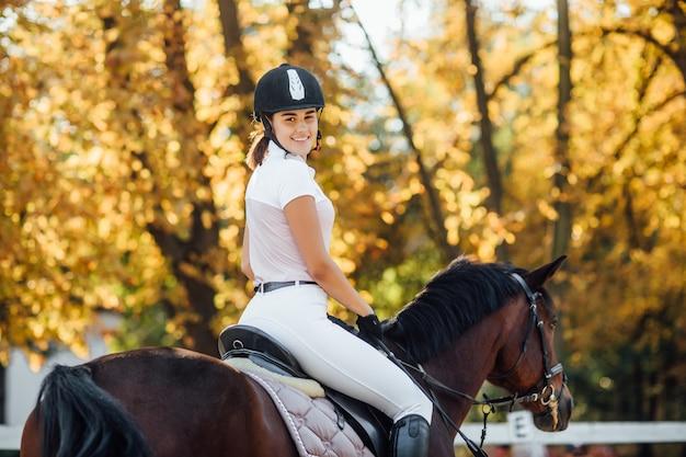 Foto van een mooie jonge vrouw die een paard berijdt in een zwarte helm en laarzen.