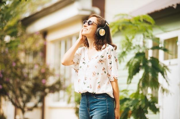 Foto van een mooie jonge vrouw, die een zonnebril draagt, muziek met een koptelefoon luistert en ervan geniet