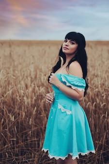 Foto van een mooie jonge vrouw die op een groot veld loopt en geniet van warm zomerweer