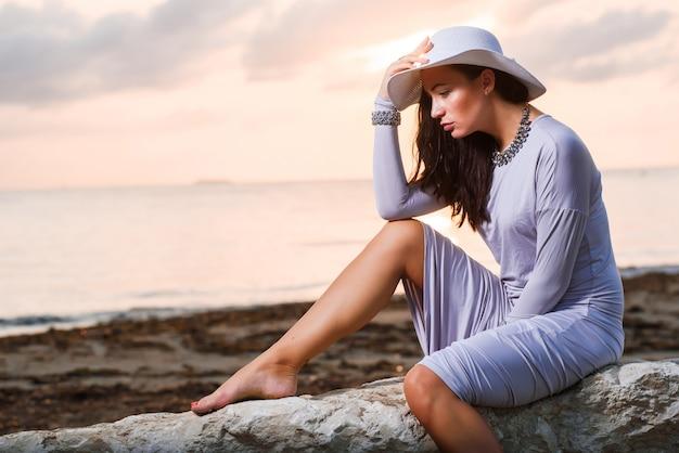 Foto van een mooie jonge vrouw in een hoed aan zee