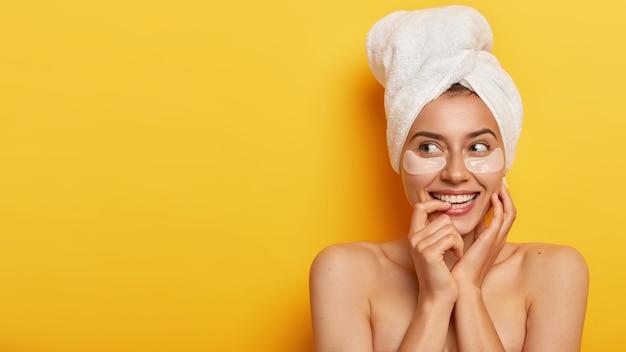 Foto van een mooie jonge vrouw met een frisse, gezonde huid, kijkt weg, heeft schoonheidsprocedures, staat blote schouders tegen gele muur, geeft om haar lichaam, voedt de huid, draagt patches voor zachtheid