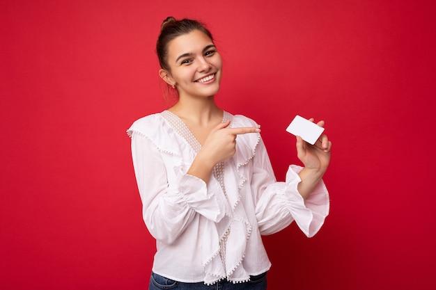 Foto van een mooie positief lachende jonge donkerblonde vrouw die een witte blouse draagt, geïsoleerd over een rode achtergrond met een creditcard die naar de camera kijkt en een vinger wijst naar een plastic contactloze kaart.